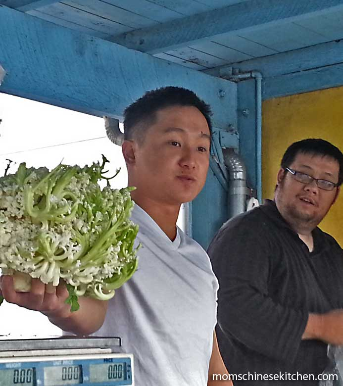 A vendor at the Alemany Farmers Market shows off a head of Chinese cauliflower.